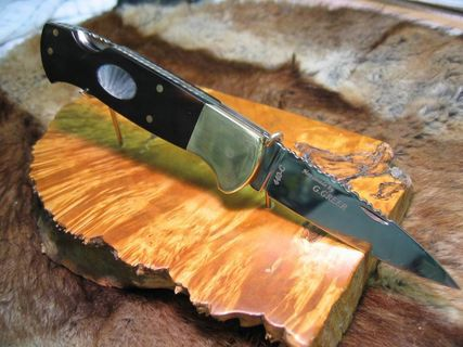 Buffalo horn folding knife with brass bolsters and mother of pearl inlays