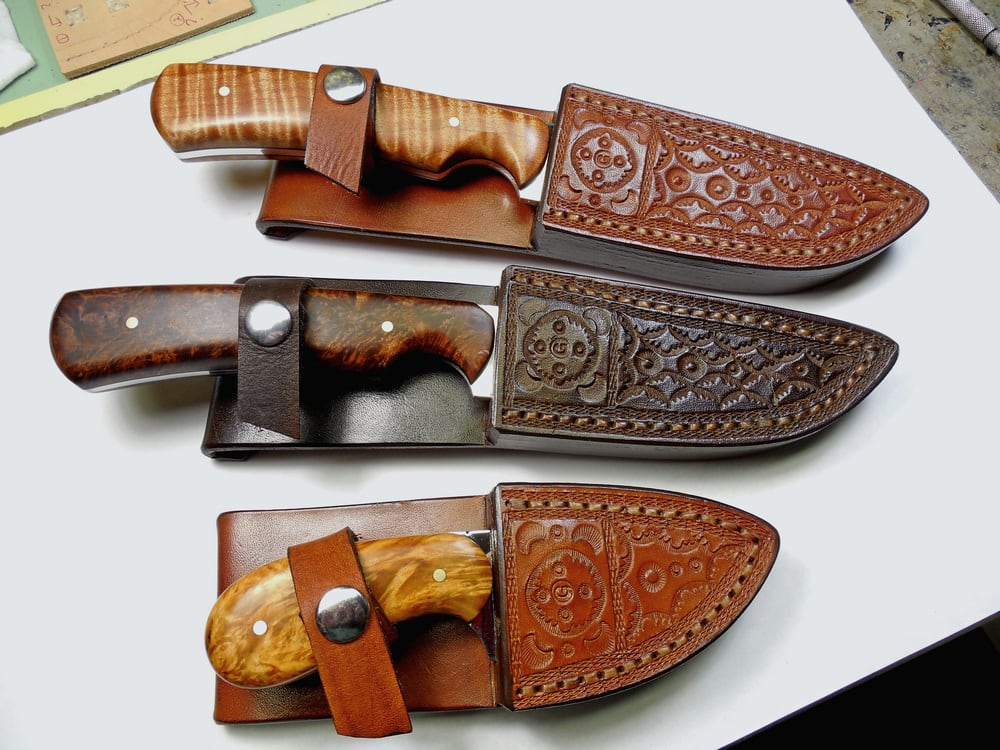 Three completed custom fitted, welted sheaths