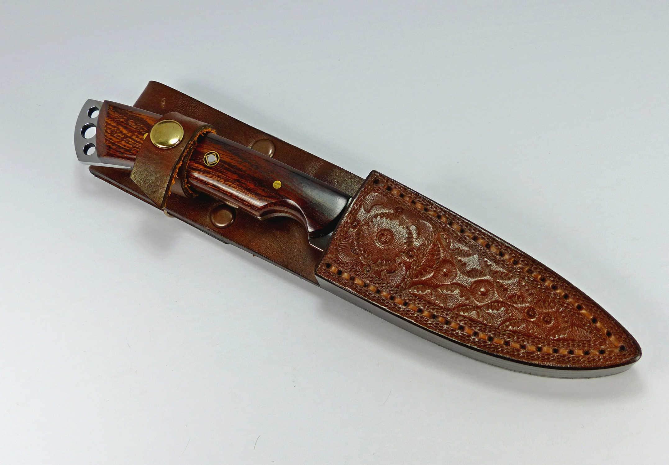 Fixed blade sportsman knife inside custom fitted brown leather sheath