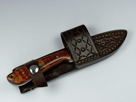 Brown handled knife inside handmade brown leather sheath
