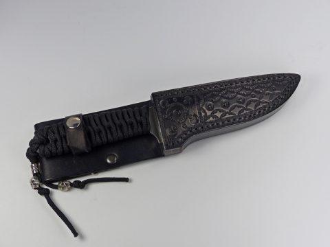 Black paracord knife inside black sheath