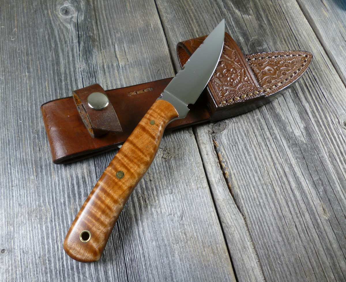 Knife with brown colored wood handle resting on leather sheath on grey background