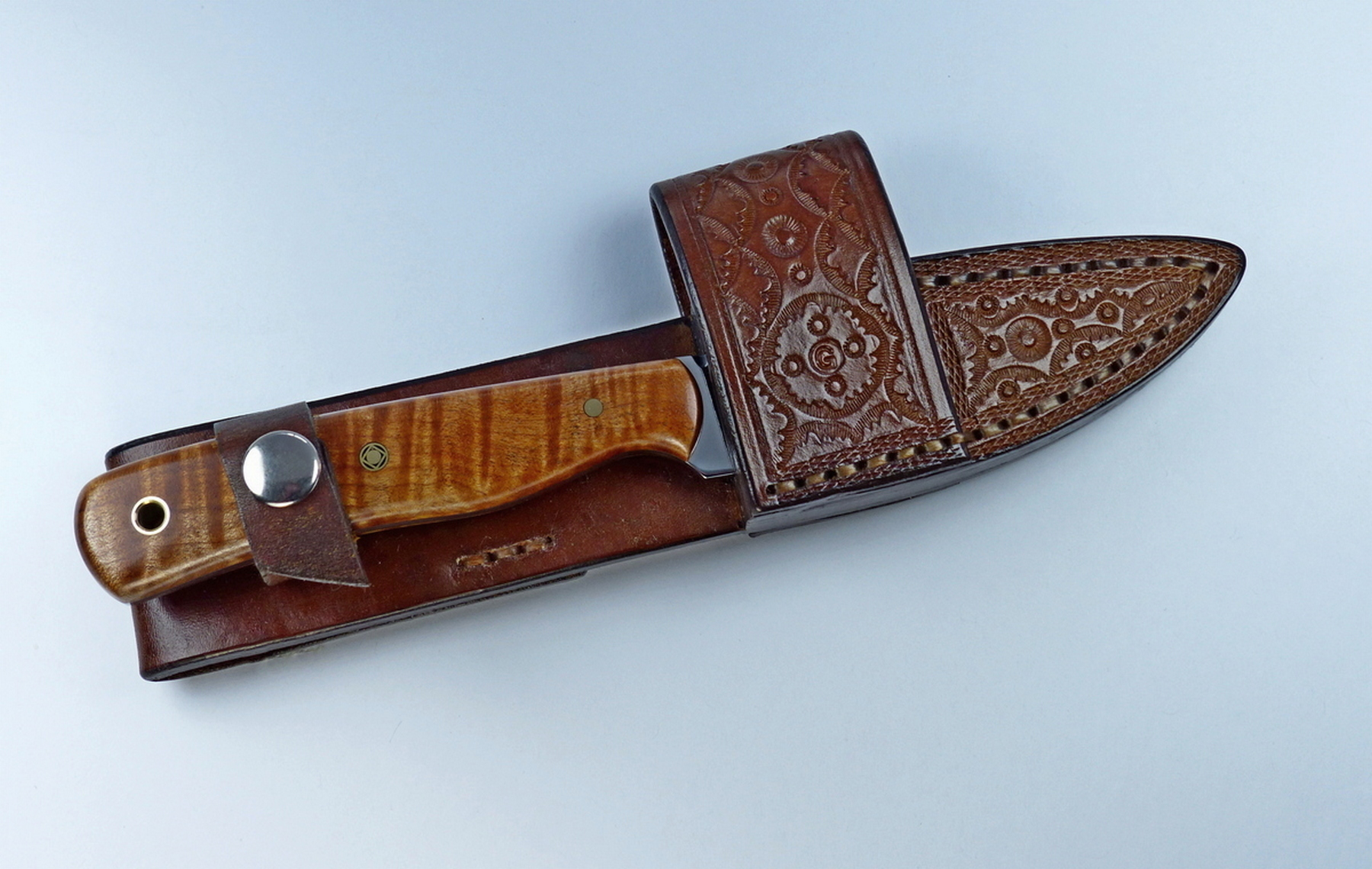 Brown colored EDC knife inserted inside leather cross draw sheath