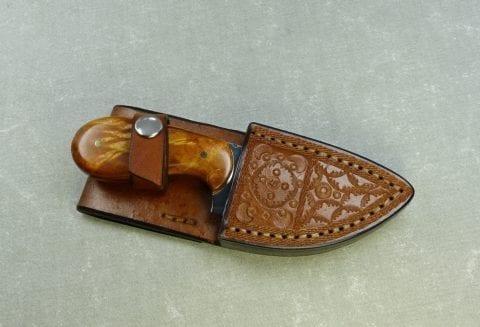 Small maple hunting knife inside handmade leather sheath