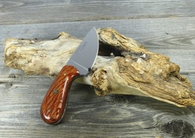 Small hunting knife made of stripped wood resting on driftwood