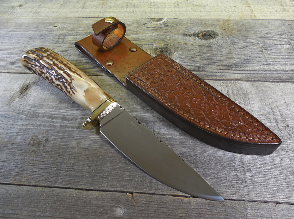 Elk horn hunting knife beside custom fitted leather sheath
